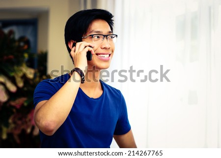 Smiling Asian man talking on the phone at home - stock photo