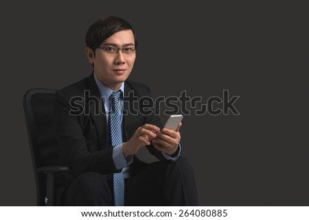 Smiling Asian manager using smartphone and looking at the camera