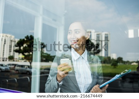 Smiling Asian manager with a mobile phone looking through the window - stock photo