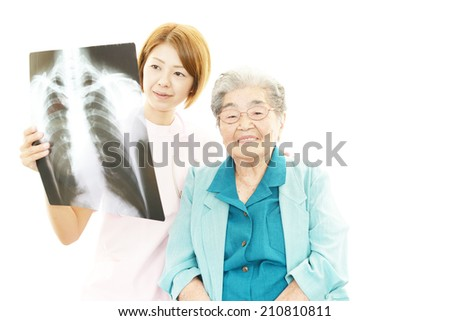 Smiling Asian medical doctor and senior woman - stock photo