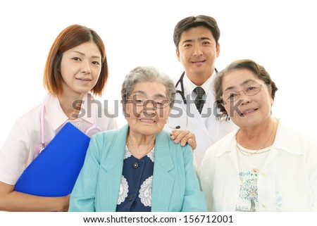 Smiling Asian medical staff and senior women - stock photo