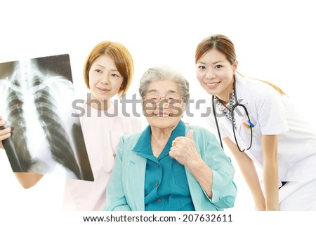 Smiling Asian medical staff with old woman - stock photo