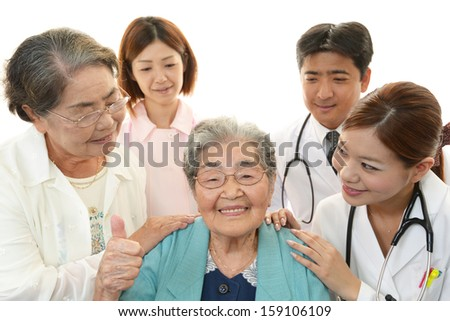 Smiling Asian medical staff with old women - stock photo