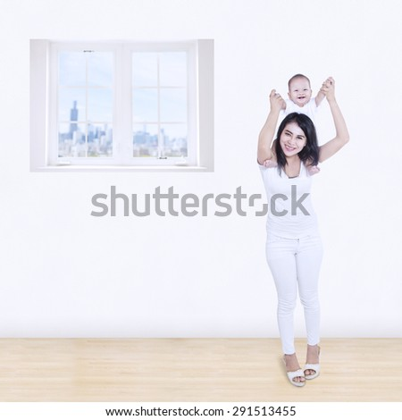 Smiling asian mom playing with her baby at home - stock photo