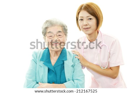 Smiling Asian nurse with old woman - stock photo