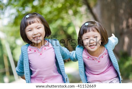 smiling asian twin girls with flying pose - stock photo