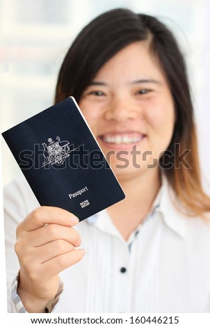 Smiling Asian Woman Holding an Australian Passport in narrow focus - stock photo