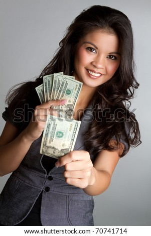 Smiling asian woman holding money - stock photo
