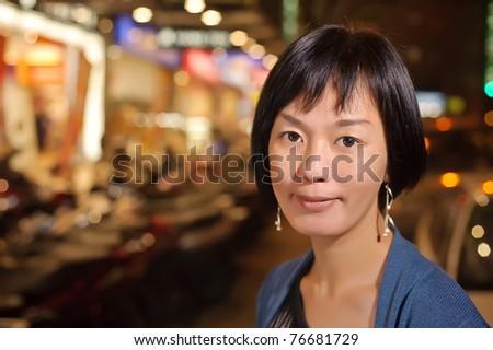 Smiling Asian woman in modern city night, half length closeup portrait on dark and illuminated urban background. - stock photo
