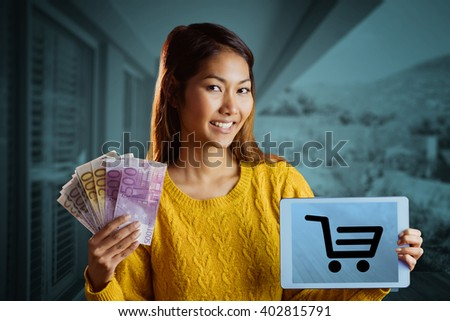 Smiling asian woman showing tablet and bank notes against stylish outdoor patio area - stock photo