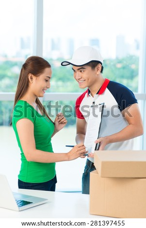 Smiling Asian woman signing for receiving packages - stock photo