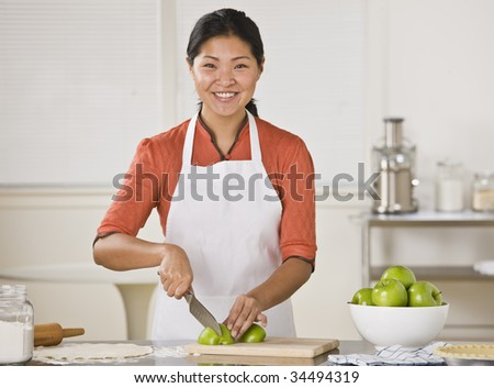 Smiling Asian woman standing at counter and slicing apples.Horizontal - stock photo