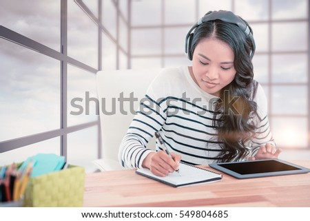 Smiling Asian woman with headphones writing on notepad against blue sky seen through window
