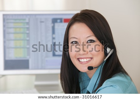 Smiling Asian woman with headset and computer monitor - stock photo