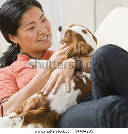 Smiling Asian woman with puppy on her lap. Square. - stock photo
