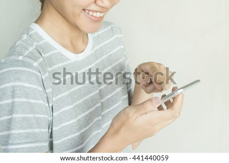 Smiling Asian women holding mobile communication phone, selective focus on hand - stock photo