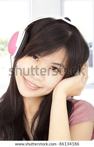 smiling asian young girl listening to music - stock photo