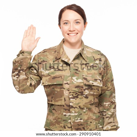 Smiling at oath of enlistment. Attractive female Army soldier wearing multicam camouflage. - stock photo