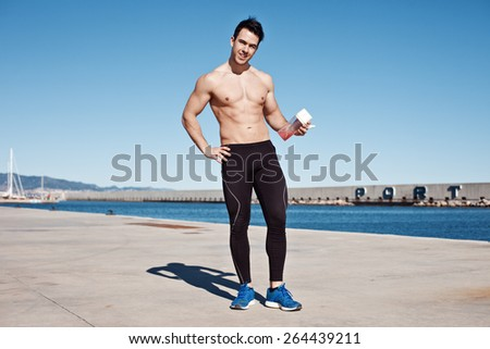 Smiling athlete with naked torso with protein cocktail - stock photo