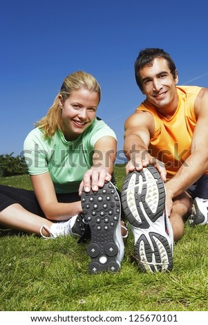 Smiling athletic man and woman stretching their hands down to the soles of their trainers while limbering up before exercise