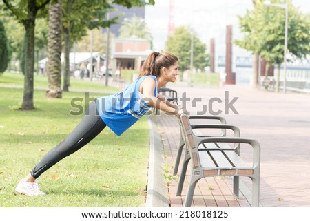 Smiling athletic woman doing push ups in the street, healthy lifestyle concept. - stock photo