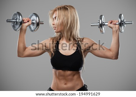 Smiling athletic woman pumping up muscles with dumbbells on gray background - stock photo