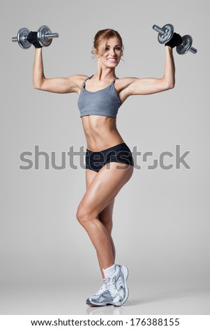 Smiling athletic woman pumping up muscules with dumbbells on gray background - stock photo