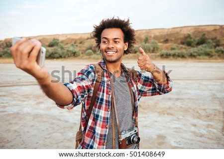Smiling attractive african man taking selfie with mobile phone and showing thumbs up