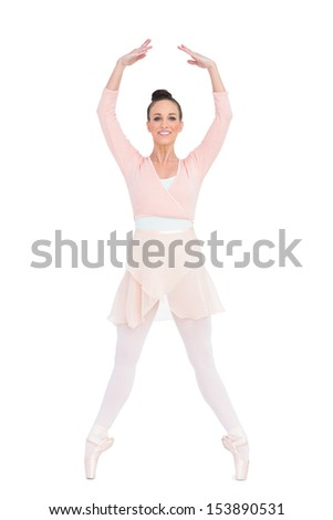 Smiling attractive ballerina standing on her tiptoes on white background