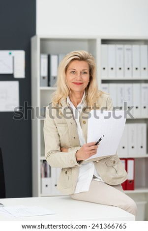 Smiling attractive blond middle-aged businesswoman sitting on the edge of her desk in the office holding a written report in her hand