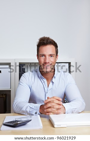 Smiling attractive business man sitting in office at desk - stock photo