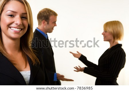 Smiling attractive business woman in focus with two business people having a conversation behind her out of focus - stock photo