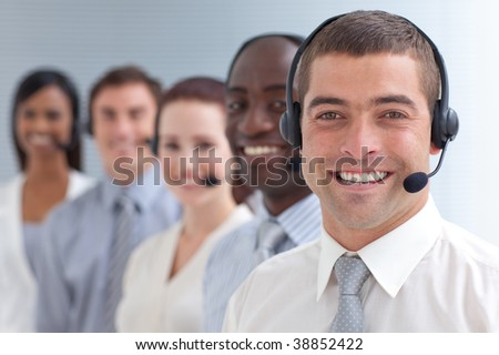 Smiling attractive businessman standing  in a call center in a line