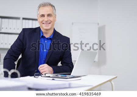 Smiling attractive businessman with a confident beaming smile sitting at his desk in the office working on paperwork