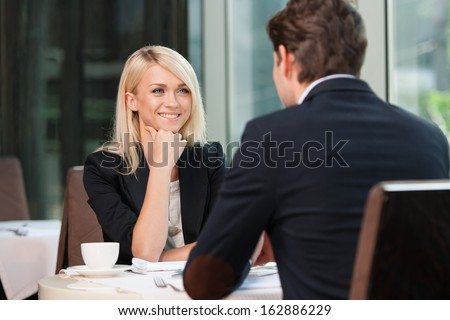 Smiling attractive businesswoman and man having discussion. While drinking coffee at lunch break  - stock photo