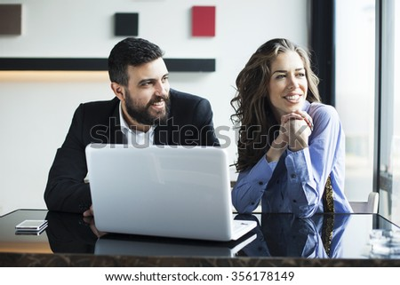 Smiling attractive businesswoman and man having discussion. While drinking coffee at lunch break. Businessman And Businesswoman Meeting In Coffee Shop. Shallow depth of field - stock photo