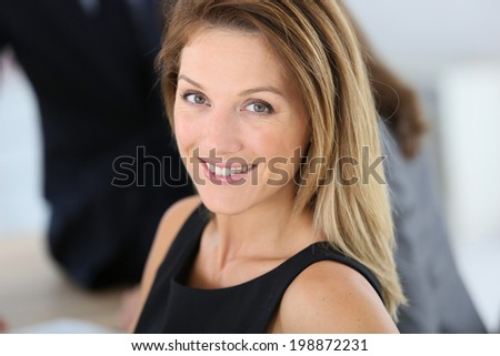 Smiling attractive businesswoman attending meeting - stock photo