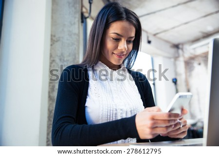 Smiling attractive businesswoman using smartphone in cafe - stock photo