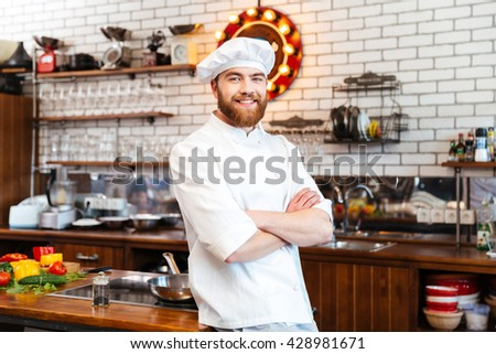 Smiling attractive chef cook with beard standing with hands folded on the kitchen  - stock photo