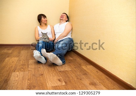 Smiling attractive couple sitting on floor in home
