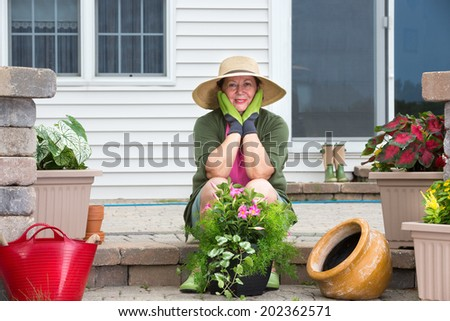 Smiling attractive elderly woman pausing while potting up plants on the steps of her patio in her wide-brimmed sunhat and gardening gloves to look thoughtfully at the camera with her chin on her hands - stock photo