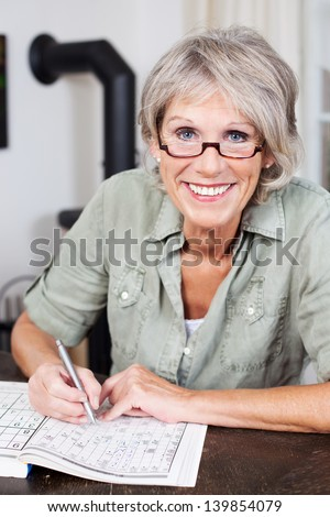 Smiling attractive elderly woman wearing glasses sitting at a table doing a crossword puzzle in a book