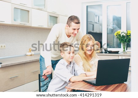 Smiling attractive family couple with son using laptop at home in the kitchen - stock photo