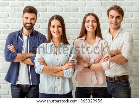 Smiling attractive group of young people standing with crossed arms, against a background of a brick wall - stock photo