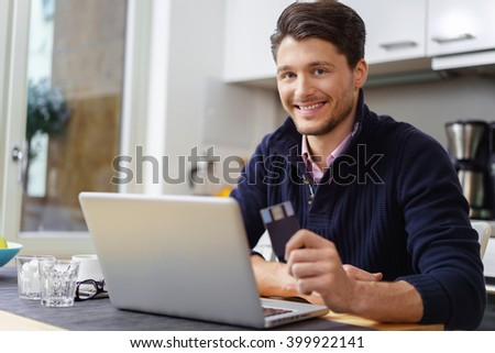 Smiling attractive man working on his laptop at home sitting at a table in the kitchen as he works from home