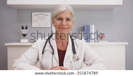 Smiling attractive mature female doctor talking to camera patient POV  - stock photo