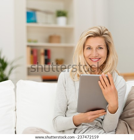 Smiling attractive middle-aged blond woman sitting on a couch at home holding a tablet-pc and looking at the camera - stock photo