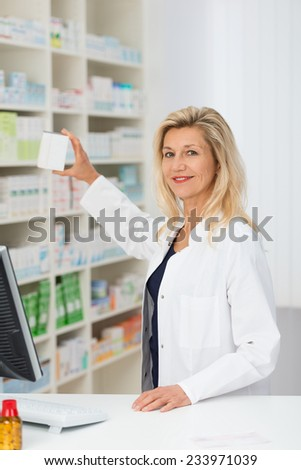 Smiling attractive middle-aged female pharmacist displaying stock in the pharmacy holding up a blank white box - stock photo