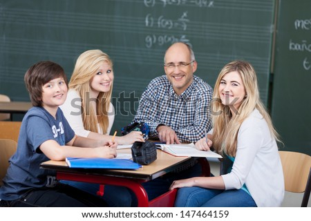 Smiling attractive middle-aged male teacher and his young teenage students in a group activity sitting around a table having a discussion, group portrait smiling at camera - stock photo