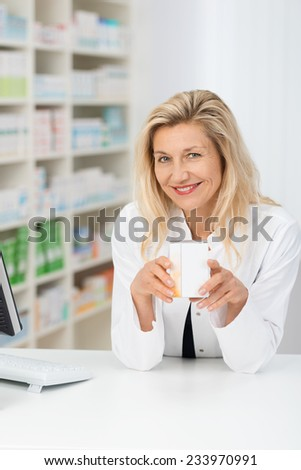 Smiling attractive middle-aged woman pharmacist displaying a box of tablets or a product in her hands as she stands behind the counter alongside shelves of stock - stock photo